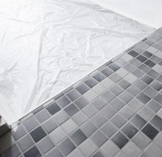 Graue kleine Mosaikfliesen sind auf dem Boden in den Bädern gelegt worden